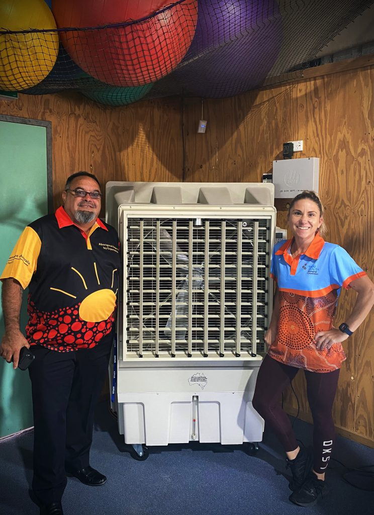 Two people pose in front of industrial air conditioner